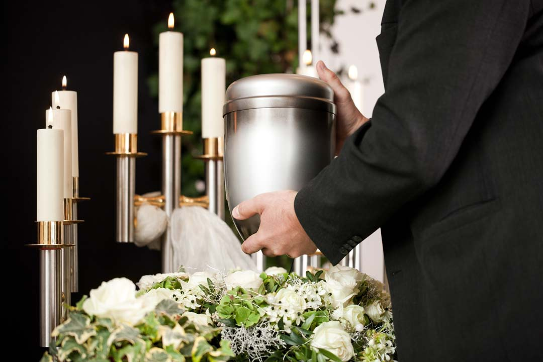 cremation-urn-with-flowers-around-and-attendent.